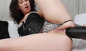 Raven-haired camgirl with tattoos fucks herself with Herculean sinister dildo
