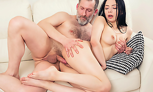 Experienced but still strong man thrusts his dick deep come into possession of a fresh throat and pussy of his younger brunette girlfriend from behind.